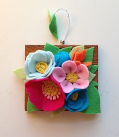 Pretty, petite felt flower hanging art. Wool blooms, set on miniature wooden plaque. Perfect for any small space that needs some brightening.