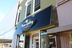 Flower Gallery Dimensional letters installed onto a raised panel with custom aluminum architecture awnings on the front of the Flower Gallery building in downtown Concordia, KS Dimensional Lettering Laser Cut Acrylic Awnings