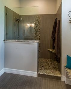 This master bathroom features a walk-in shower with a partial glass enclosure and taupe wall tiles. A pebble tile accent strip on the shower wall matches the floor, while the neutral tiles that are used within the shower are also used to cover the bathroom floor outside of the space.