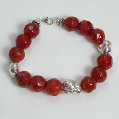 "Handmade gemstone carnelian bracelet features a strand of semi-precious faceted and nugget carnelian gemstones, sterling silver accent beads, wire band, and lobster claw clasp. 8"" in length. Add a nec"