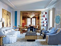 A Manhattan living room transformed by architect Mark Stumer and designer James Aman features (from left) an Alex Katz portrait, a Robert Mangold abstract work, a Donald Judd wall sculpture, and a butterfly painting by Hirst; the tabletop train sculpture is by Jeff Koons, and the antique rug is from Doris Leslie Blau.
