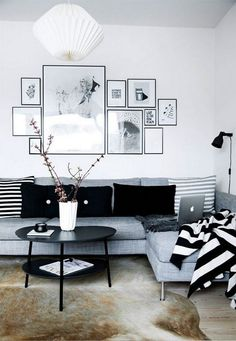 Nice living room idea with grey corner sofa, black&white wall art, black round coffee table and black floor lamp