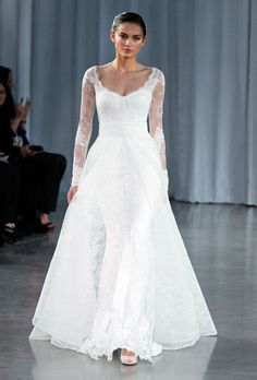 A modest Monique Lhuillier gown with long lace sleeves and a tulle overskirt reveals a woman's curves with the lace corset.