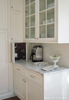 Love the Clever Corner Cabinet Storage for appliances, honed Carrara marble countertop, Benjamin Moore Super White walls and trim, glass front Chrstiana Cabinetry, Restoration Hardware pulls and knobs