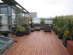 moderne Dachterrasse mit Holz-Bodenbelag und Kies-Deko