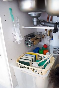 Under sink organizing. Hang wire basket from nails and it is easy to pull out to remove items.
