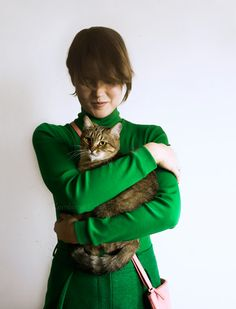 Young woman in green wear standing with cute tabby domestic cat in her hands, human and cat by Abrakadabra photo