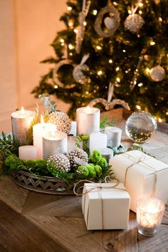 Centro navideño de velas y verde, y regalos sobre mesa de centro (306636)