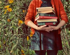 A giant stack of books = happiness. Add a cardigan and some yellow flowers and it just might be perfection.