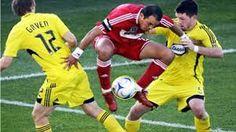En esta jugada podemos observar a este jugador el cual levanta el balón con las piernas para pasar a sus dos contrincantes , mientras los dos intentan frustrar la jugada .