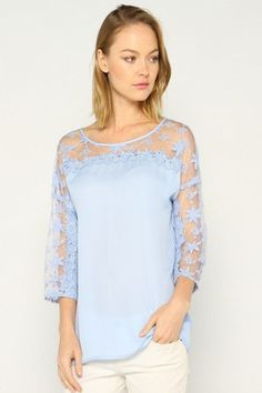 """A romantic lace top that has ...PEARLS! Check out the detail on this top, you get absolutely everything! The baby blue lace is so sweet, and the pearls are just a cherry on top! Don't forget about the sweet button detail on the back. A great blouse when you want to dress up but not actually wear a dress!  Approx. measurements: 23.5"""" longMaterial: 100% Polyester   