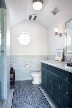 The pristine guest bathroom features beautiful tile in shades of gray. A subway tile backsplash continues around half of the room, while intricate basketweave tile is underfoot. The dark vanity with its beadboard-inspired front is dressed up with metallic hardware and an undermount sink.