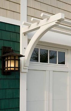 Garage detail: Carriage house door, arbor and light fixture. Get the look with a Clopay Coachman Collection garage door, Design 11, REC14 windows. by sondra