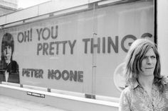 """Bowie in front of a billboard featuring advertisement for Peter Noone's cover of Bowie's """"Oh! You Pretty Things"""""""