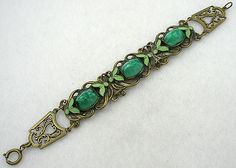 "Czech Art Nouveau brass link bracelet; the three center links have a curling vine motif set with a tall peaked green swirl glass glass stones, each stone flanked by lime green enameled pairs of leaves. The end links finishing the bracelet have a more ornate brass design. Attributed Czechoslovakia.   Size:  7"" x 3/4"""