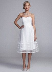Elegant and ultra-chic, you will look amazing on your special day in this lace and tulle gown!  Straplessbodice features ultra-femininedipped neckline.  Lace band detailing creates a flattering silhouette.  Tulle A-line tea length skirt gives this gown a whimsical feel.  Fully lined. Back zip. Imported polyester. Dry clean only.