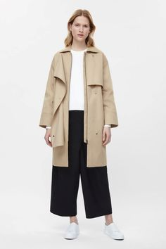 A classic design with modern proportions, this trench is made from cotton twill with a laser cut traditional storm flap. A relaxed fit, it has tonal press buttons, a detachable belt and large welt pockets.