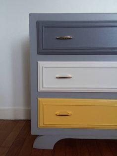 Petite commode vintage totalement remise aux goûts du jour. Elle vous séduira par sa petite taille, lui permettant de se glisser facilement dans n'importe quelle pièce. Ses trois tiroirs possèdent néanmoins un beau volume de rangement. Parfaite pour une chambre d'enfant ou une petite pièce. Le contour est en gris clair, les côtés et l'un des tiroirs sont en gris plus soutenu. Le second tiroir est en blanc et le troisième est en jaune. Ils sont interchangeables selon vos envies. Le tout est…