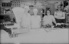 Kaksi nuorta myyjätärtä ja päivettyneet nainen ja paidaton mies hymyilevät makkaroita ja lihaa notkuvan myyntitiskin takana sekatavarakaupassa Tammentiellä eli nykyisellä Tammitiellä Nummenmäessä. Hyllyillä on esimerkiksi keksejä ja sokeria. Kuvaaja: H. Attila, 1930.  VA9810:5712