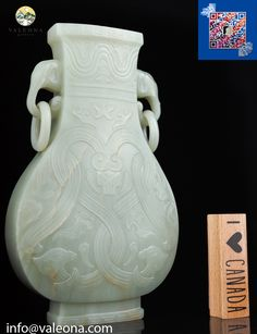 """Chinese Antiques Auction: A pale celadon archaistic jade vase 18th c. $30000 ( Qianlong, Beijing Imperial Workshop) The pattern works contain elephant head for handles and suspended rings. And it is carved in relief with an interwoven stylized pattern of archaic dragons. Under the rim, there is a wide wavy band. The color of stone is translucent light celadon color. 8 1/2""""h, 21.8 cm"""