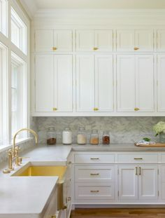 White stacked kitchen cabinets adorning vintage brass latch hardware are fixed above a marble backsplash lining white shaker cabinets topped with a gray Brass Kitchen, Kitchen Cabinet Hardware, Kitchen Redo, New Kitchen, Kitchen Dining, Kitchen Knobs, Kitchen With Brass Hardware, Faucet Kitchen, Kitchen Layout