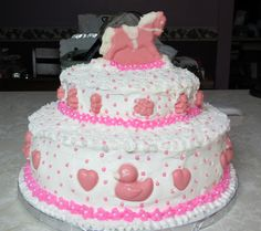 Baby Shower Cake with all edible decorations.  The rocking pony topper, baby items, hearts and ducks are made from white chocolate.  White and pink candy pearls were also used.