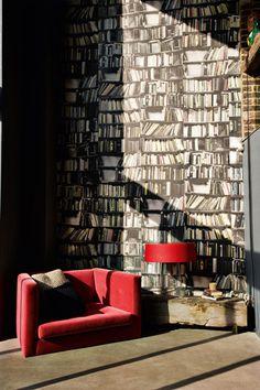 La considerable altura del salón resalta aún más con el fondo del papel con imágenes de libros, de Deborah Bownes. Dos toques de rojo: el sofá, de George Smith, y la lámpara mod. Glam T3, de Prandina, animan la decoración