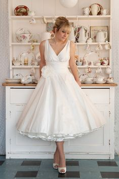 """Milan"" gathered, cross-over bodice with ""Julietta"" tea length skirt, made in ivory silk dupion, as a dress, with gathered waist panel, ivory ribbon-edged 1950s petticoat and silk rose. Design your own gown at www.app.carolinearthur.com"