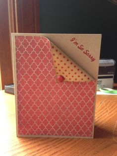 """I'm so sorry"" peeking out from behind the folded patterned paper that has been lightly inked with a red brad to keep everything securely in place."