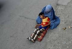 A veiled Afghan woman waits with her son, whose legs have been amputated, for alms on a street in Kabul, August 4, 2008.   This is heartbreaking.