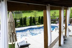 Hanging Outdoor Drapes- Use inexpensive chain link fencing materials to create curtain rods to hang outdoor drapes on.