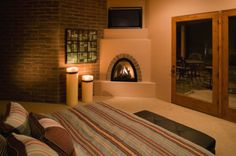 Adobe Dreaming - An adobe fireplace mixes beautifully with a brick wall and wood trim. Southwestern Style Decor, Southwestern Home, Southwestern Decorating, Adobe Fireplace, Small Fireplace, Fireplace Ideas, Fireplace Lighting, Bedroom Fireplace, Awesome Bedrooms
