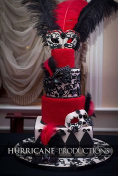 Black, white and red masquerade themed cake with feather accents.