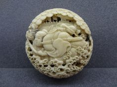 Netsuke (manju). Warrior pursuing dragon. Made of ivory.