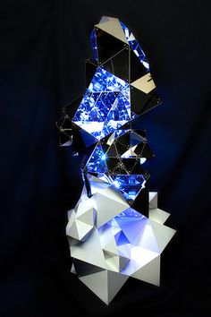 The Geode Tower Lamp is a large sculptural lighting object. Built as an assembly of identical modular units, the piece is essentially a building system of lighted blocks. Its geometric surface continually dissolves and reappears as it reacts to light emitted from its interior. Programmed illuminated patterns are transmitted and distorted across the network, as the light bounces to create infinite spatial configurations.