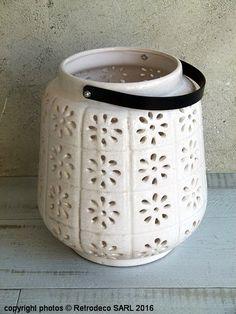 Très jolie lanterne en céramique blanche ajourée motif fleurs qui illuminera vos soirées. A disposer sur une marche ou sur un meuble pour une déco pleine de charme. Une création Light & Living. Anse en métal noir. A s'offrir ou à offrir.