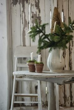 Christmas Simple~ ironstone pitcher full of green branches and white candles in pots.