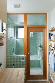 グリーンのグラデーションのタイルが美しいバスルーム。トイレ・洗面室との間をガラス張りにすることで、開放感たっぷり。