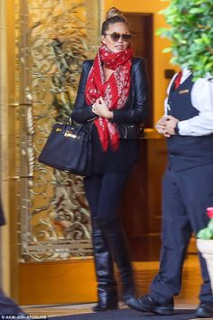 So chic: The mother-to-be hid her baby bump under a long red scarf and looked stylish in l...