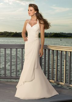Stunning halter wedding dress with assymmetrical styling to create a slimming look with draped details!