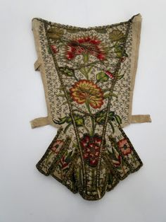 Stomacher, early 18th century, inner part dating c. mid 17th century. Cream silk with floral embroidery in polychrome silk threads, edges and front flap are bound in silk criss crossed cord, linen lining with a design of undulating vines, acorns of fruit and leaves.