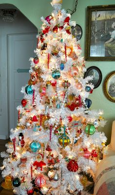 white Christmas tree decorated completely in vintage ornaments.