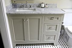 Beautiful gray green bathroom design with gray green bathroom cabinets, white carrara marble counter top, polished nickel hardware, white