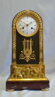 French Empire antique mantel clock in ormolu, patinated bronze and marble signed Mesnil. - Gavin Douglas Antiques