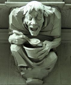 Gargoyle ....man eating from a bowl: Morningside Heights. The Britannia at 527 West 110th Street. New York