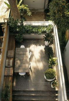 Private courtyard uses a u-shaped configuration with full length bench seating and dining table. Love the wall of pot plants for privacy and added greenery.