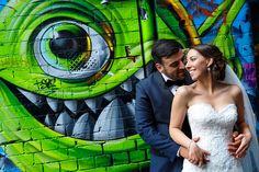 bride and groom having their wedding photography at Hosier Lane in Melbourne, graffiti on the wall