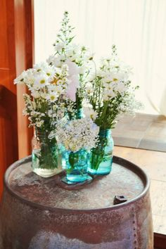Rustic wedding decor: Mason Jar Centerpeices. Blue jars with baby's breath and daisies. Simple and cheap!