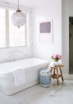 Unwind after a long day with a hot and steamy bath in this beautiful white bathtub. Pair a modern tub with marble floors, natural light, and an elegant, one-of-a-kind chandelier. The only thing that could make this bath experience any better is a refreshing glass of iced espresso to sip while you relax.