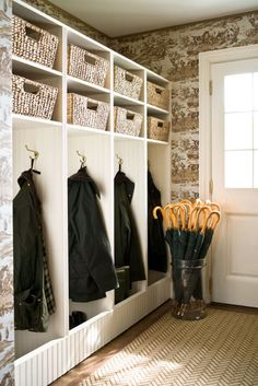 a well-stocked mudroom: brollies and Barbours.